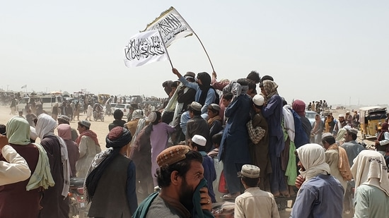 People wave Taliban flags as they drive through the Pakistani border town of Chaman on July 14, 2021.(AFP)