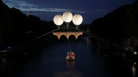 """A view of an art installation by French artist Olivier Grossetete titled """"The Farnese Bridge"""", showing a Michelangelo-inspired cardboard bridge floating above the Tiber river, suspended by three balloons, in Rome, Italy. (REUTERS/Yara Nardi)"""