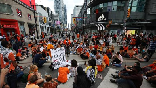 People occupying space at Yonge and Dundas street, after the discovery of hundreds of remains of children at former indigenous residential schools, on Canada Day in Toronto, Ontario, on July 1, 2021. (REUTERS)