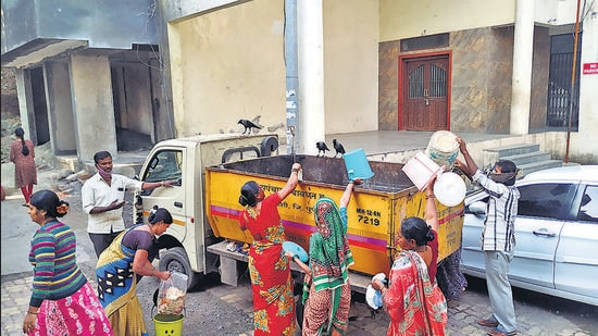 Residents of Bavdhan Budruk, one of the merged villages in PMC, dispose of garbage in garbage collection van provided by the gram panchayat. BJP seeks legal recourse to keep DP for merged villages in PMC's hands (HT)