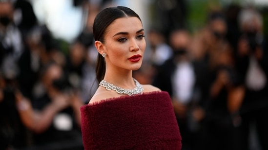 Amy sported bloody coloured nails, lipstick, a heavy contour and dramatic eyeliner to complete her stunning red carpet look.(AFP)