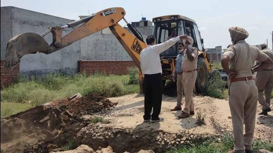 Demolition of illegal structures in progress in Giaspura area of Ludhiana on Thursday. (HT Photo)