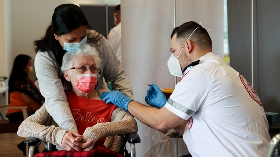 An elderly woman receives a booster shot of her vaccination against Covid-19 at an assisted living facility, in Netanya, Israel.(Reuters)