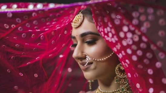 Disha tied her hair in a tight bun and it was covered with her netted dupatta.  She wore a huge gold choker necklace with intricate designs and green beads around it, she also wore a tika, earrings, which needed to be secured in her hair (Instagram/IsraniPhotography)