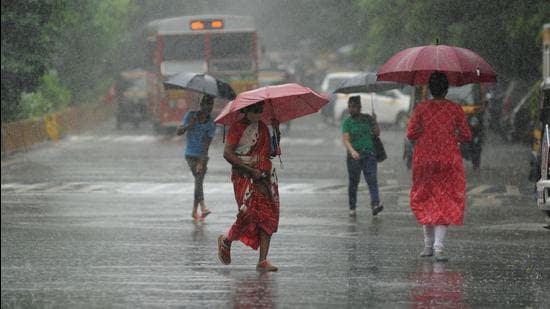 People walk amid heavy downpour in Kandivali, Mumbai. (HT PHOTO)