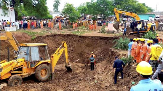 People look on during a rescue operation after several people fell into a well during the rescue of a girl who had fallen into it, at Lal Patthar in MP's Vidisha district. (PTI Photo)