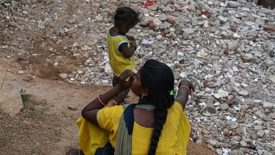 A woman with a child sit near the debris of houses after local authorities razed a settlement that was said to be in a forest land in Khori village at Faridabad district. (AFP)