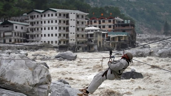 A man is pulled across to safety on a rope, as damaged buildings and the Alaknanda river are seen in the background in Uttarakhand.(Reuters/ File photo)