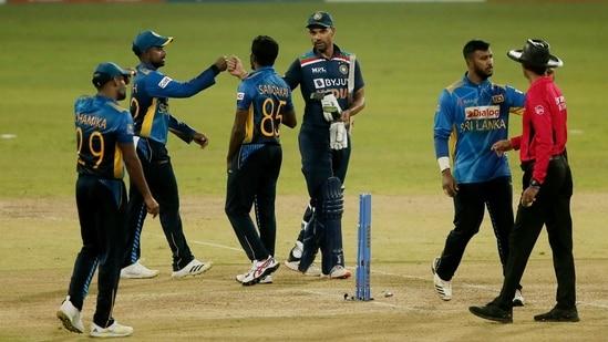 India's Shikhar Dhawan with Sri Lanka's Lakshan Sandakan and teammates after India won the match.