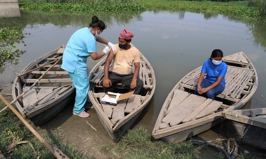 A health worker administers a vaccine for COVID-19 to a boatman on an island in the River Yamuna in New Delhi. (AP Photo)