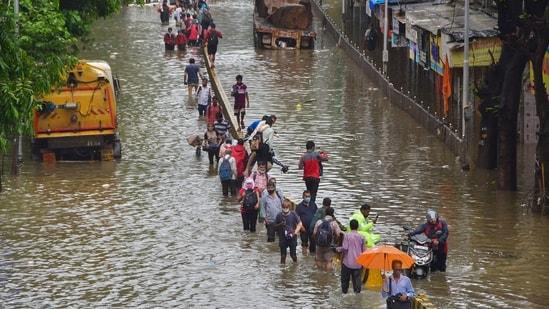 Commuters wade through a waterlogged street after heavy rain at Dadar in Mumbai on Sunday,(PTI)
