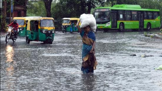 A woman carries a sack while walking through a waterlogged road in New Delhi on Monday, July 19. (ANI)