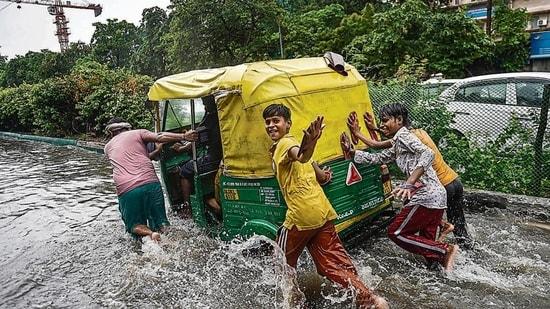 People push an autorickshaw through a waterlogged street following heavy rains, near ITO in New Delhi. (PTI Photo)