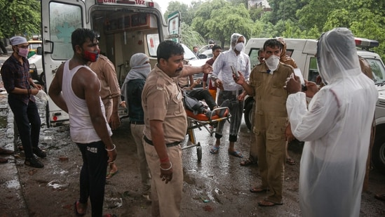 Delhi police personnel investigate the spot where a 27-year-old drowned after waterlogging at Pul Prahladpur in New Delhi.( Sanchit Khanna/ Hindustan Times)