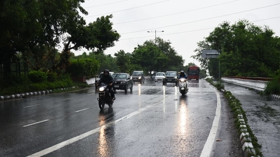 People head to work in Delhi near ITO as it rains on Monday morning. Monsoon in Delhi has been delayed by over two weeks.(HT Photo/ Ajay Aggarwal)