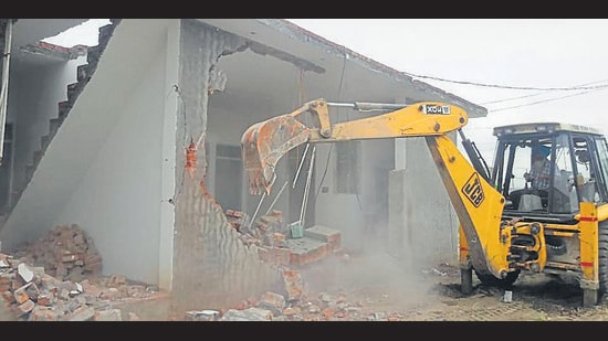 An illegal construction being razed in Giaspura area of Ludhiana on Monday. (ht photo)
