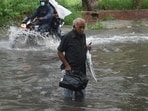 An elderly commuter attempts to cross a waterlogged stretch near ITO in New Delhi, on July 19. After a weeks-long wait, the hot, humid days in Delhi on July 19 gave way to the season's first spell of heavy rain, which proved to be a nightmare for motorists and commuters across the city.(Raj K Raj / HT Photo)