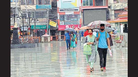 People walk on a road in Mandi amid rain on Tuesday. The red alert has been issued for Mandi, Shimla, Kangra, Kullu and Chamba districts. (Birbal Sharma/HT)