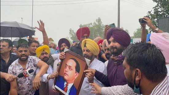 The rain was no deterrent as newly appointed Punjab Congress chief Navjot Singh Sidhu and Kuljit Singh Nagra, one of the four working presidents, hold up a portrait of Dalit leader Dr BR Ambedkar after visiting the museum at Bhagat Singh's native village of Khatkar Kalan on Tuesday. (HT Photo)