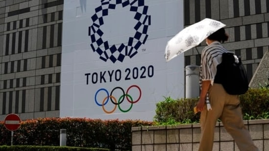 A woman wearing a protective mask walks with an umbrella to shield from the sun walks in front of a Tokyo 2020 display at Tokyo Metropolitan government building at the 2020 Summer Olympics, Tuesday, July 20, 2021, in Tokyo(AP)