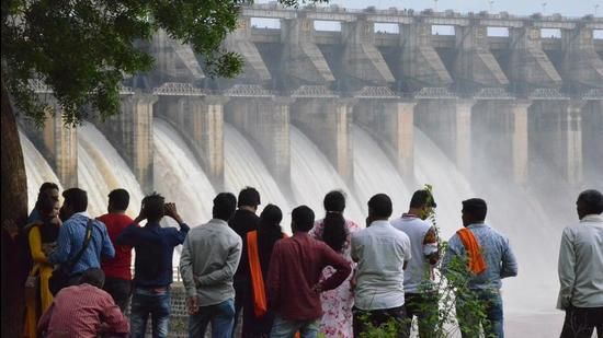 This photo taken on July 24, 2018 shows people watching water pour out of seven of 21 gates of the Bargi Dam that were opened after excess rain in Jabalpur in India's central Madhya Pradesh state. Bargi Dam on the Narmada River in Madhya Pradesh is one of the first completed dams along the waterway. / AFP PHOTO / - (AFP)
