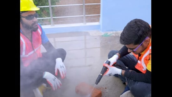 The image shows two men trying to cut a brick with a waterjet.(YouTube/@Crazy XYZ)