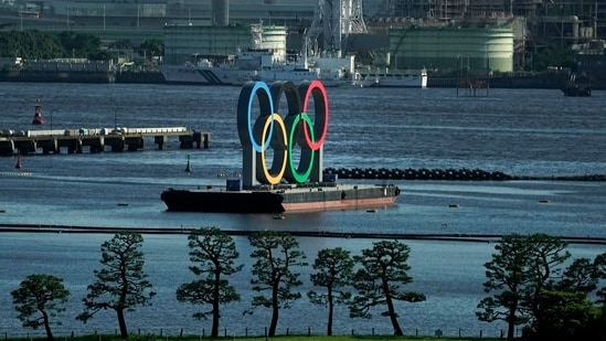 A barge with the Olympic rings mounted on it floats in the water ahead of the 2020 Summer Olympics(AP)