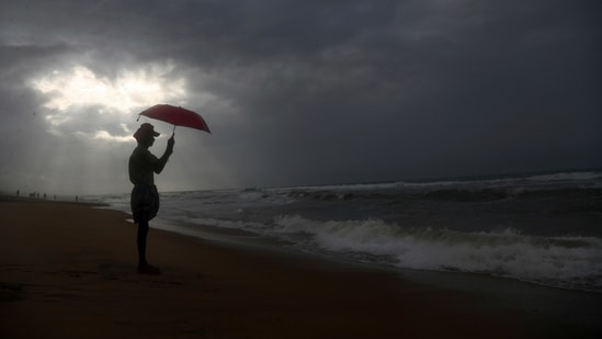 A man holds an umbrella as it rains on the beach by the Bay of Bengal coast in Visakhapatnam, Andhra Pradesh state, India, Thursday, July 15, 2021.(AP)