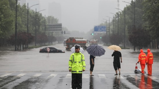 Police officer standing guard in front of a flooded street following heavy rains in Zhengzhou in China's central Henan province.(AFP)