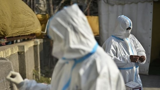 Health workers in PPE coveralls working at a temporary coronavirus testing facility set up at Sarai Kale Khan in New Delhi.(Biplov Bhuyan / HT file photo)
