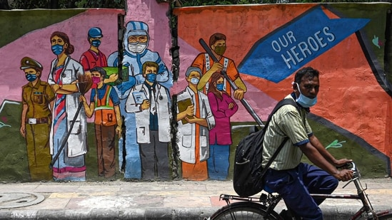 A cyclist passes by a wall mural depicting frontline Covid-19 coronavirus workers, in New Delhi on June 29 (AFP).