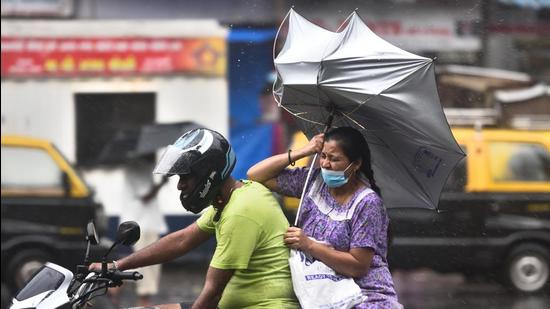 The umbrella of a woman riding pillion turns upside down amid heavy rain and gusty winds. (Satish Bate/HT PHOTO)
