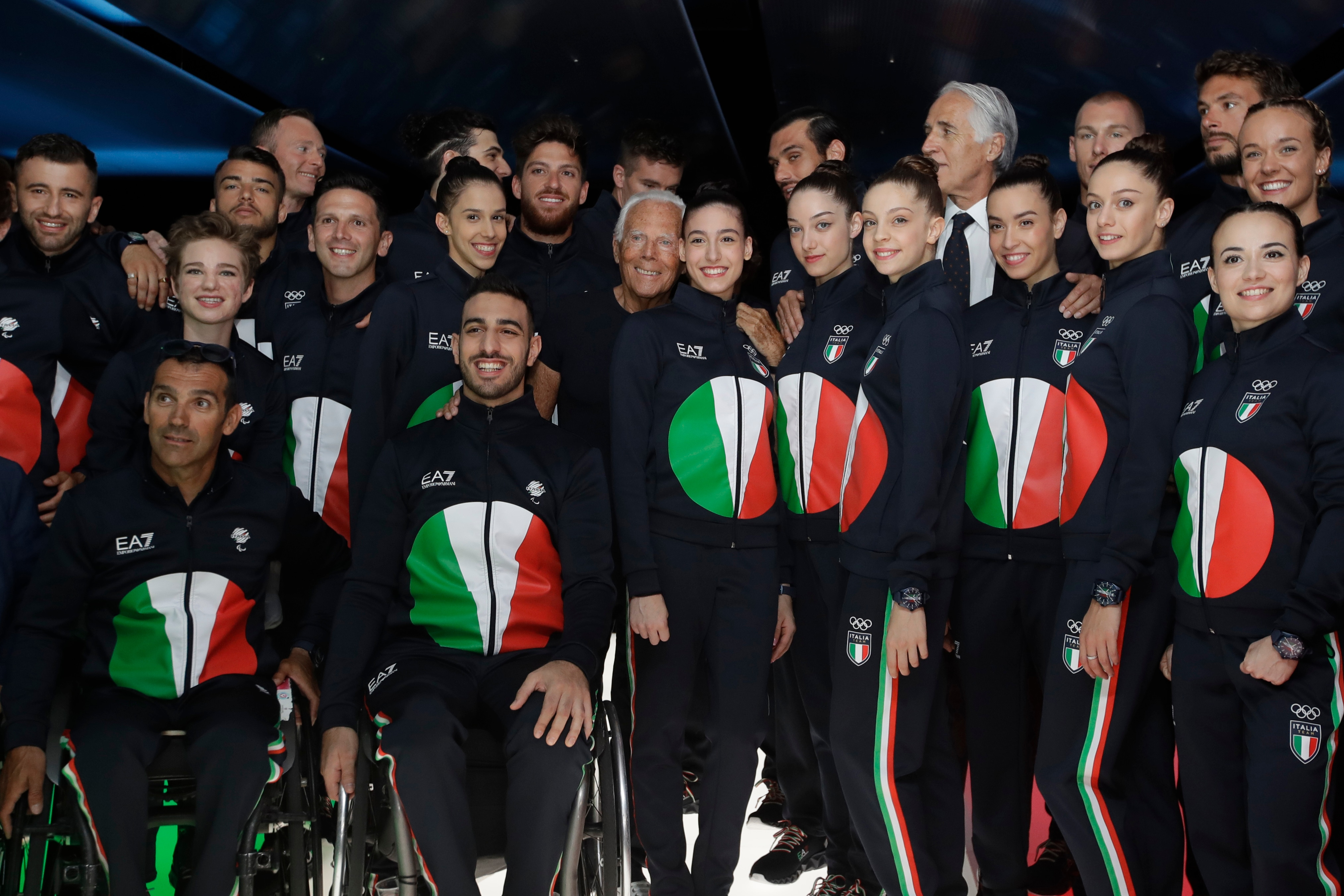 FILE - In this June 15, 2019 file photo, designer Giorgio Armani, centre, poses with Italian Olympic athletes at the end of the Emporio Armani men's Spring-Summer 2020 collection, unveiled during the fashion week, in Milan, Italy. Emporio Armani decked out Italy's team in track suits with a reinterpretation of Japan's rising sun in the colors of the country's flag: red, green and white.The Olympics in Tokyo open July 23, when the world's athletes will march behind their flag-bearers. (AP Photo/Luca Bruno)(AP)