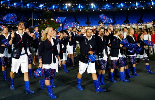 FILE - Athletes from Czech Republic parade during the Opening Ceremony at the Summer Olympics on July 27, 2012, in London. Olympic gear makes for lively social media fodder, starting with the hours-long Parade of Nations. The year's wait due to the pandemic has given enthusiasts extra time to ponder what they love or hate. Shown are the country's loud umbrellas and neon blue Wellington boots.(AP)