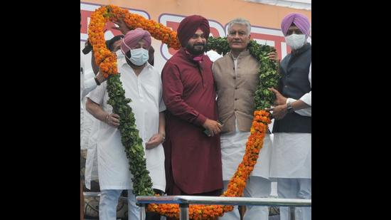 Navjot Singh Sidhu after taking over as Punjab Congress president from Sunil Jakhar (right) with chief minister Capt Amarinder Singh by his side at the state Congress Bhawan in Chandigarh on Friday. (Ravi Kumar/HT)