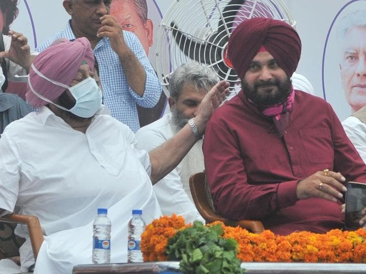 Chief minister Capt Amarinder Singh congratulating Navjot Singh Sidhu on his elevation as the Punjab Congress chief in Chandigarh on Friday. (Ravi Kumar/HT)