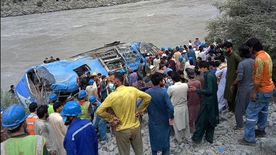 Rescue workers and onlookers gather around a wreck after a bus plunged into a ravine following a bomb explosion, which killed several passengers including nine Chinese nationals, in Kohistan district of Khyber Pakhtunkhwa province on July 14, 2021. (AFP)