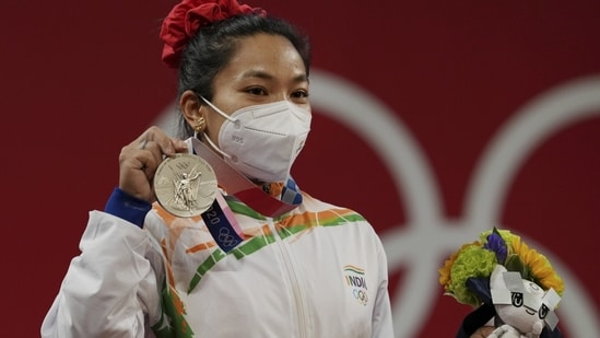 India's Mirabai Chanu wearing Olympic Rings ear-ring poses for photographs while standing on the podium after receiving the silver medal in women's 49 kg category weightlifting event at the Summer Olympics 2020, in Tokyo, Saturday, July 24, 2021.(PTI)