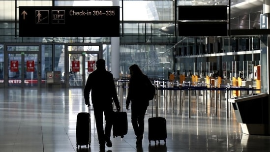 People walk through a deserted check-in hall at the airport in Munich, Germany.(Representational image/AP)