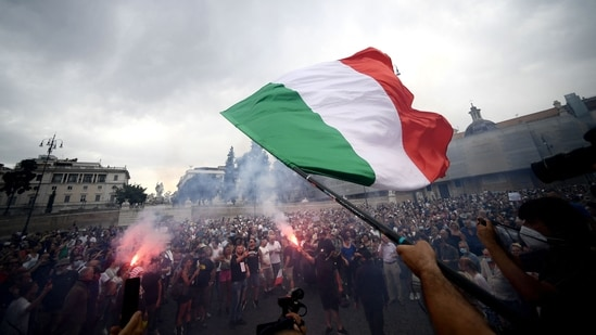 A protester holds an Italian flag as he takes part in a demonstration in Piazza del Popolo in Rome.(AFP)