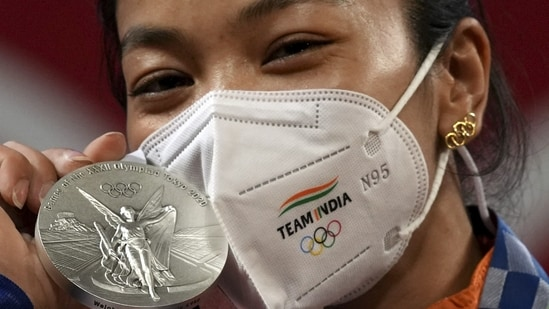 Tokyo Olympics 2020: India's Mirabai Chanu, wearing golden Olympic Rings ear-ring, poses for photographs while standing on the podium after receiving the silver medal in women's 49 kg category weightlifting event at the Summer Olympics 2020, in Tokyo.(PTI)