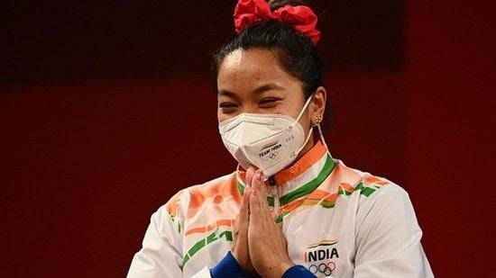 Silver medallist India's Mirabai Chanu gestures on the podium.