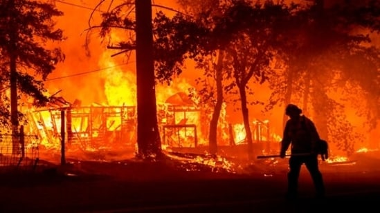 Firefighter passes a burning home as the Dixie Fire flares in Plumas County, California.(AP)