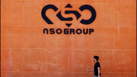 A man walks past the logo of Israeli cyber firm NSO Group at one of its branches in the Arava Desert, southern Israel. (REUTERS)