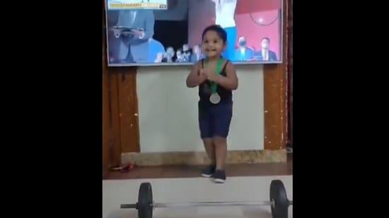 The image shows the little girl imitating Mirabai Chanu.(Twitter@imsathisholy)