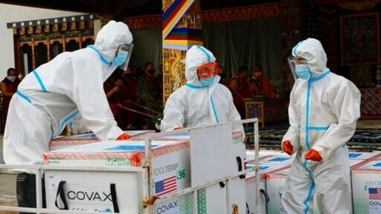 This photograph provided by Unicef shows airport personnel in protective suits handle unloaded consignment as 500,000 doses of Moderna Covid-19 vaccine gifted from the United States arrived at Paro International Airport in Bhutan, July 12, 2021. (Unicef via AP)