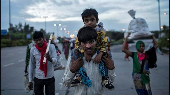 A migrant worker carries his son as they walk along a road with others to return to their village, during the first nationwide lockdown to limit the spreading of coronavirus disease (Covid-19), in March last year, New Delhi. (REUTERS File)