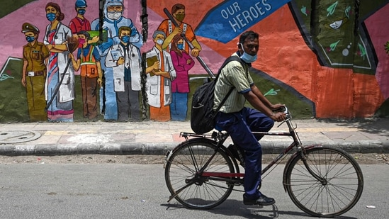 A cyclist passes by a wall mural depicting frontline Covid-19 coronavirus workers, in New Delhi.(Money Sharma / AFP)