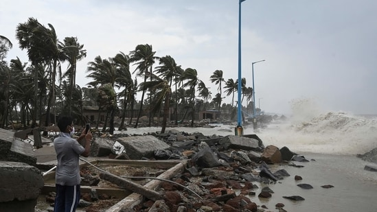 A man takes pictures as waves lash over onto a damaged shoreline during Cyclone Yaas. (AFP)