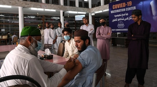 A health worker inoculates a student with a dose of the CanSino Biologics' Covid-19 coronavirus vaccine at Jamia Naeemia seminary in Lahore. (AFP)